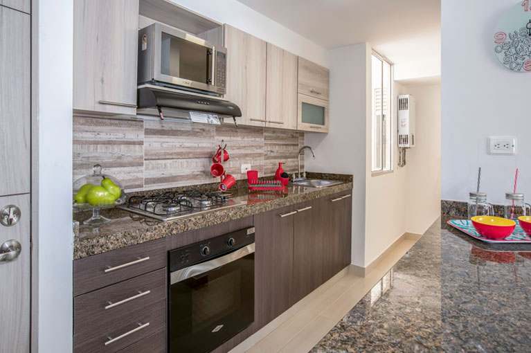 Integral kitchen with microwave oven at Arboleda del Parque residential project in Bogota